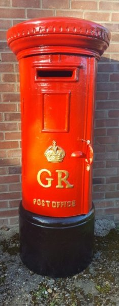A full size large red pillar post box for wedding and event hire